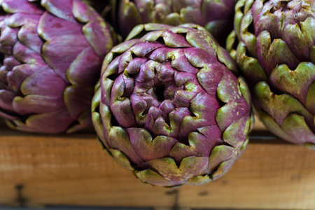 Fresh big Romanesco artichokes green-purple flower heads ready to cook seasonal food Stock Photo