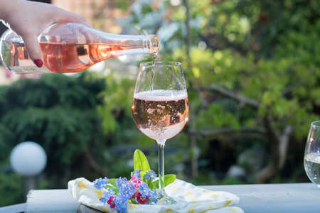 Waiter pouring a glas of cold rose wine, outdoor terrase, sunny day, green garden background Stock Photo