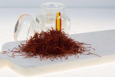 Rohes organisches rotes Safran-Gewürz auf Marmorplanke Standard-Bild - 76081702