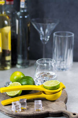 vitamine: Lime manual press for preparation of cocktails, limes and glass with ice cubes, party time Stock Photo