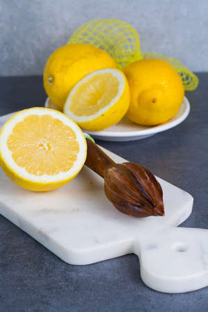 Ripe juicy yellow lemons witn juicer stick made from olive tree wood
