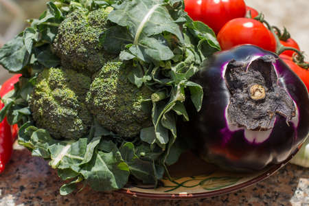Ripe violet eggplant ball with broccoli and red tomatoes, fresh healthy vegetables ready to cook