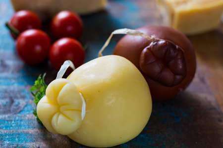 Traditional Italian hard cheese Provolone of Caciocavallo on wooden background