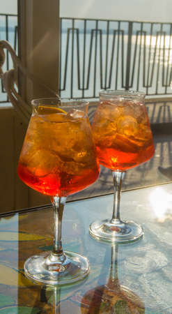 Waiter prepared the Aperol Sprits summer cocktail with Aperol, prosecco, ice cubes and orange in wine glass, ready to drink on sunny terrace with sea view