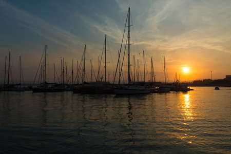ortigia: Beautiful port for luxury yachts in the rays of the setting summer sun. Sunset at the port for yachts. Yacht club Stock Photo