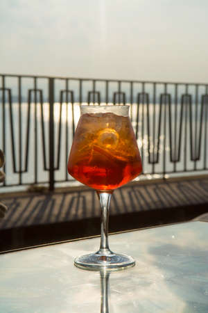 spritz: Waiter prepared the Aperol Sprits summer cocktail with Aperol, prosecco, ice cubes and orange in wine glass, ready to drink on sunny terrace with sea view