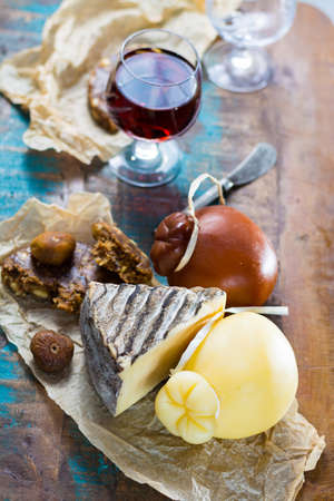 Sweet dessert liqueur wine in glass, hard cheeses Caciocavallo or Provolone, Tomme de Montagne, dried figs with figs bread, still life on wooden platter