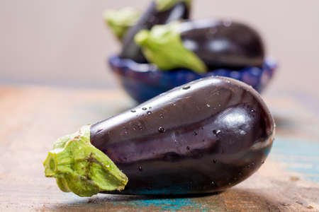 Ripe fresh raw purple eggplants on a wooden background