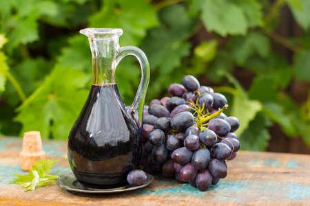 Negro viejo vinagre balsámico en una jarra de vidrio con uvas rojas frescas sobre fondo de viñedo verde en la mesa de madera, fuera