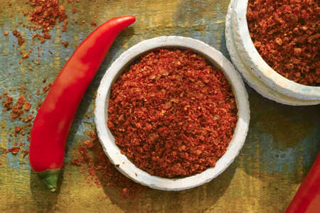 hottest: Red hot chili Cayenne pepper fresh and dried powdered spice, ready to use on wooden background Stock Photo