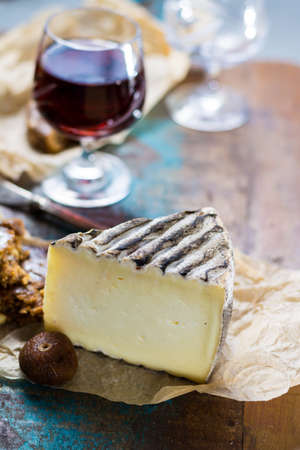 Sweet dessert liqueur wine in glass, hard French cheese Tomme de Montagne and dried figs with figs bread, still life