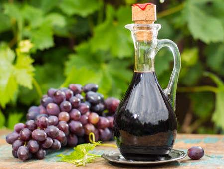Nero vecchio aceto balsamico in una brocca di vetro con uve rosse fresche su sfondo verde vigneto sul tavolo di legno, all'esterno Archivio Fotografico - 81189806