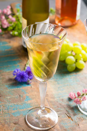 Cold summer wines, white wine, served in beautiful glass on terrace in cafe with romantic flowers, close up