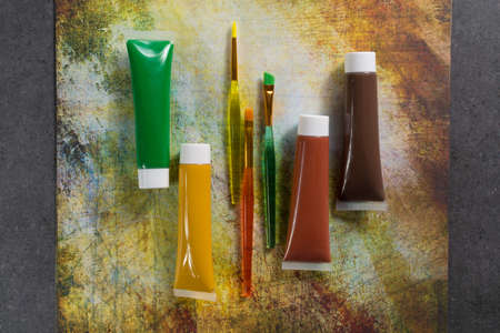 Colours of the nature - mix of green, yellow and brown - home or office interieur design concept, tubes with acrylic paint and  brushes, close up Stock Photo
