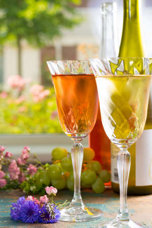 degustation: Cold summer wines, white and rose, served in beautiful glasses on the fresh air, outdoor in the green garden with flowers, sunny day, party or romantic concept