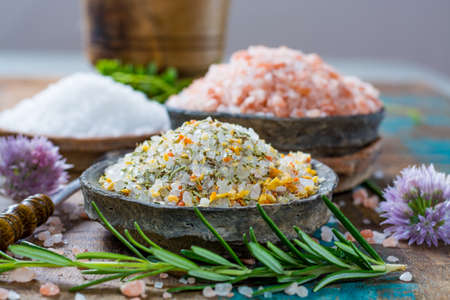Different types of natural salt in stone bowls on wooden surface. White sea salt, pink Himalayan salt, Spiced salt with rosemary