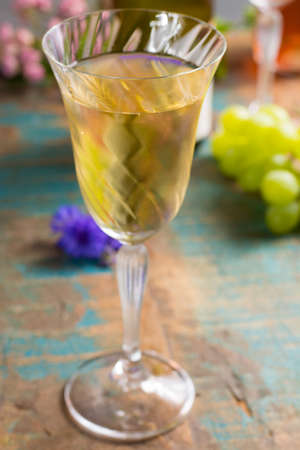 Cold summer white wine, served in beautiful glass on terrace in cafe with romantic flowers, close up