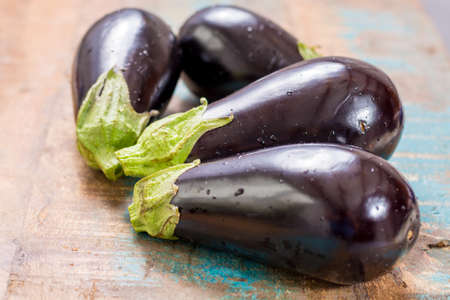 Ripe fresh raw purple eggplants on a wooden table