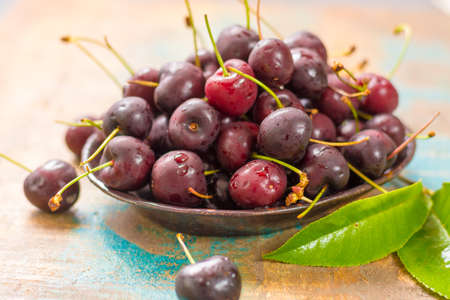 Healthy berries, fresh cold ripe black cherries in a bowl on a wooden table Stock Photo