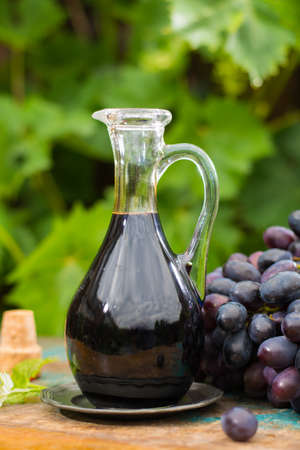 Black old balsamic vinegar in a glass jug with fresh red grapes on green vineyard on wooden table, outside Stock Photo