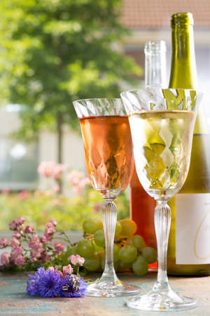 Cold summer wines, white and rose, served in beautiful glasses on the fresh air, outdoor in the green garden with flowers, sunny day, party or romantic concept