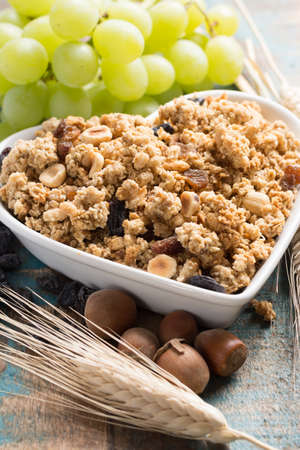 Healthy granola muesli breakfast with grape, nuts and wheat ears, love it concept, in white ceramic heart shape bowl, close up