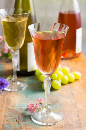 Cold summer wines, white and rose, served in beautiful glasses on terrace in cafe with romantic flowers, close up