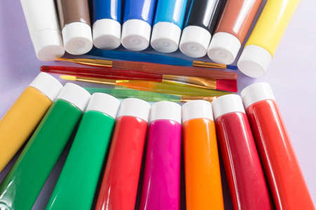 Multicolored rainbow acrylic paints tubes set with five colorful brushes - creative painters concept