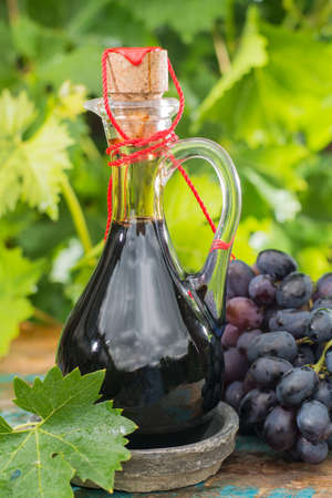 Black old balsamic vinegar in a glass jug with fresh red grapes on green vineyard background on wooden table, outside