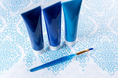 Blue, indigo, cobalt colours - home interieur design concept, on blue-white ornament, tubes with acrylic paint and blue brush Stock Photo