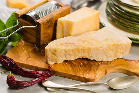 steel. milk: Aged parmesan cheese on the olive wooden board, italian food Stock Photo