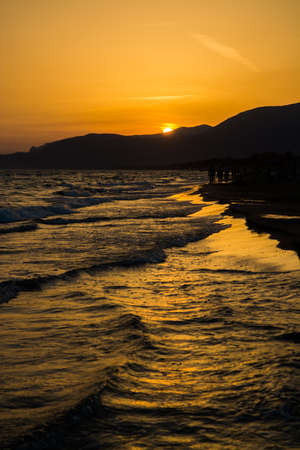 Beautiful sunset on the sandy beach, sea water with waves and silhouettes