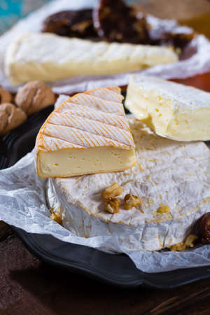 Variety of French soft cheeses - camembert, marcaire, munster, brie - delicious dessert with nuts and dried fruits