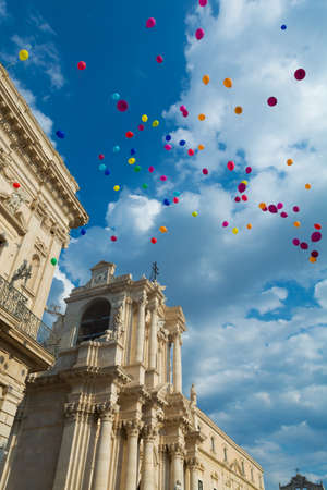 Colorful ballons and the cathedral of Siracusa, be part of the Unesco protected heritage of humanity., Ortigia, Sicily, Italy Stock Photo