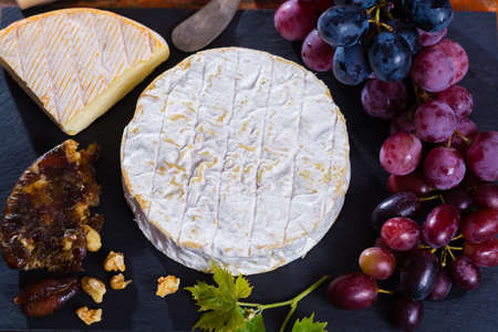 Famous French soft cheese - camembert - delicious dessert with nuts, grapes and dried fruits