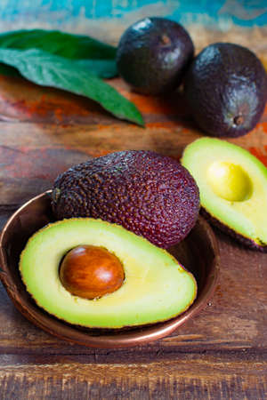 Healthy vegetarian food – green ripe avocado, new harvest, with leaves on stone plates with ornament close up