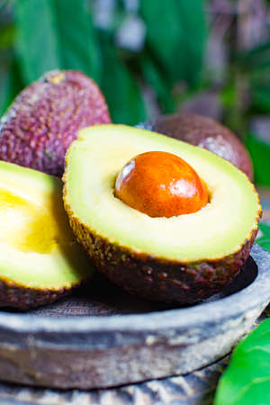 smooth: Healthy vegetarian food – green ripe avocado, new harvest, with leaves on stone plates with ornament close up