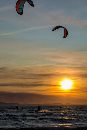 Sunset over the sea or ocean and extreme freestyle sport kitesurfing, France, Giens