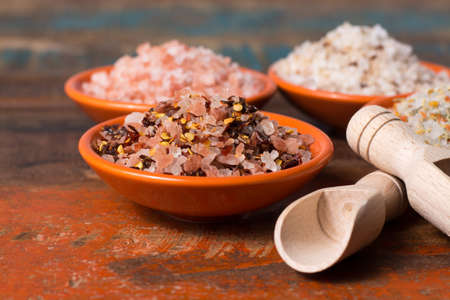 Variety of sea salt, pink Himalayan salt, colorful salt with dried chili pepper, herbs and spices  close up Stock Photo