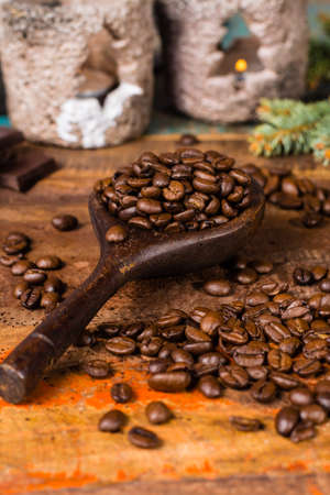 Dark roasted pure arabica coffee beans and ground coffe in old spoon on the wooden table, copy space