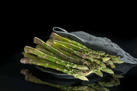 Fresh uncooked green asparagus on black background with reflection, low key, dark theme. Stock Photo