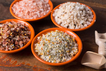 Variety of sea salt, pink Himalayan salt, colorful salt with dried chili pepper, herbs and spices  close up Imagens