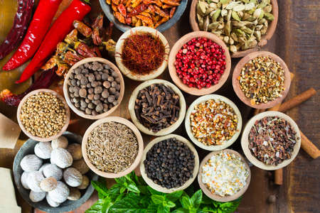 Variety of different asian and middle east spices, colorful assortment, on old wooden table, close up