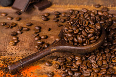 Dark roasted pure arabica coffee beans and ground coffee in old spoon on the wooden table, copy space