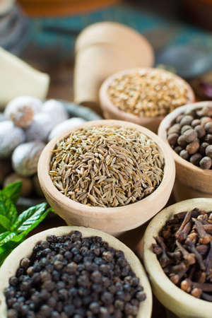 Variety of different spices with focus on ancient famous spice – dried whole cumin seeds with variety of another herbs and spices in Middle East style close up Stock Photo
