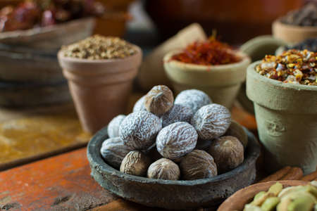 Tasty winter spice whole dried nutmeg, used as an ingredient in many dishes, eggnog, mulled wine, close up on old wooden table close up Stock Photo