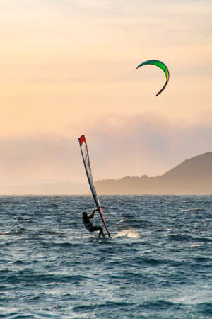 Sunset over the sea or ocean and extreme freestyle sport windsurfing, France, Giens Stock Photo