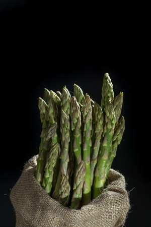 Fresh uncooked green asparagus on black background with reflection, low key, dark theme copy space