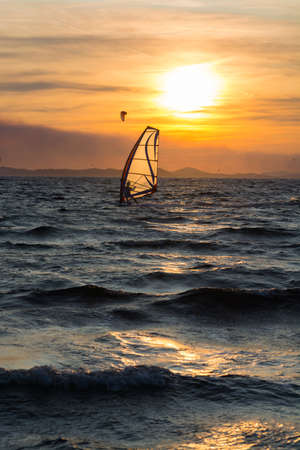 Sunset over the sea or ocean and extreme freestyle sport windsurfing, France, Giens Standard-Bild