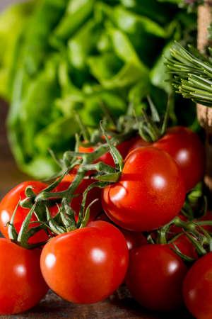 Fresh green lettuce salad, italian herbs and tasty cherry tomatoes on vine on wooden table